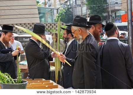 BNEI BRAK, ISRAEL- SEPTEMBER 22, 2010: Group of Orthodox Jews chooses ritual plant Lula before the holiday of Sukkot. Holiday city market