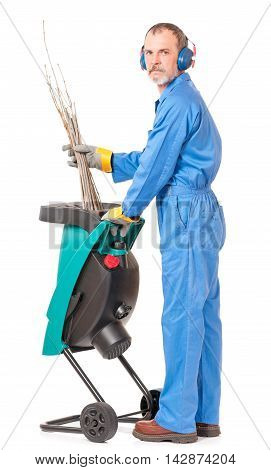 Adult worker in protective workwear near grinder for branches isolated over white background