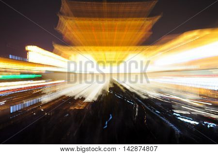A blurred image of the xian bell tower lit up at night in Shaanxi province China.