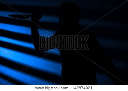 Silhouette of a Killer with a Knife at Night