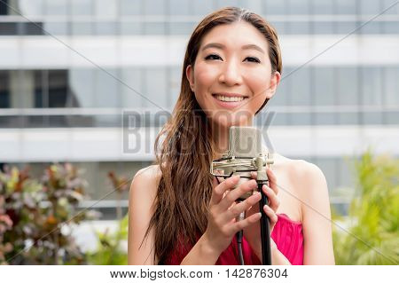 Asian Vocalist Happily Smiling And Singing With Mic On Rooftop