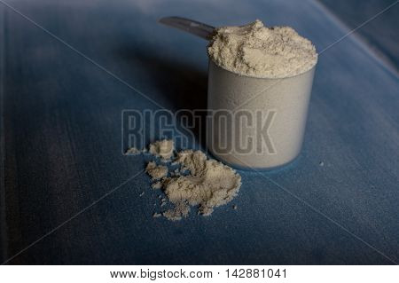 Chocolate whey protein on table with scoop