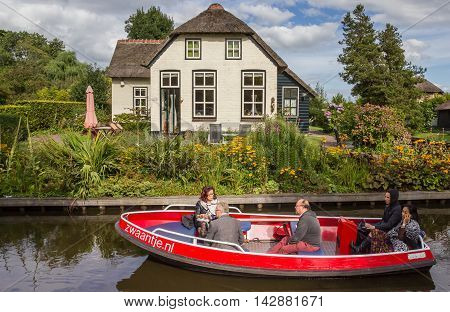 GIETHOORN, NETHERLANDS - AUGUST 9, 2016: Tourists in an electric boat in the canals of Giethoorn, Holland