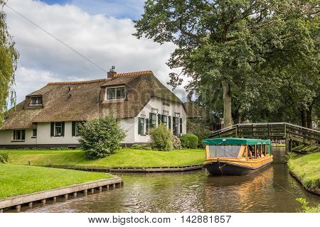 GIETHOORN, NETHERLANDS - AUGUST 9, 2016: Tourists taking a tour in the canals of Giethoorn, Netherlands