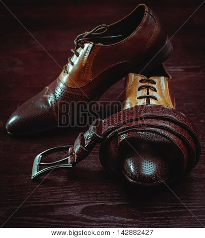 brown leather men's shoes and belt in wooden background