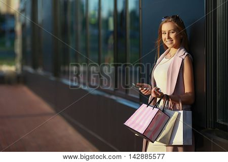 Smiling girl with shopping bags with phone in hand. Shopper. Sales.