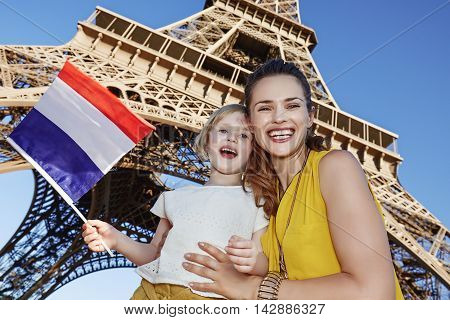 Mother And Daughter Travellers Showing Flag Near Eiffel Tower