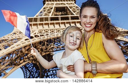 Mother And Daughter Travellers Showing Flag Against Eiffel Tower