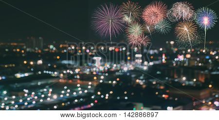 Colorful fireworks on blurred skyscrapers with city bokeh lights illuminated at night. Abstract New Year holiday or party background