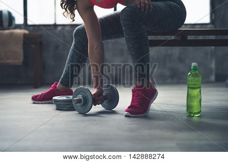 Closeup On Fitness Woman Taking Dumbbell From The Floor In Gym