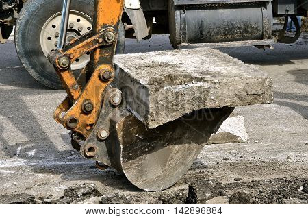 A backhoe picks up concrete slab in a demolition curbside project in a hydraulic bucket.