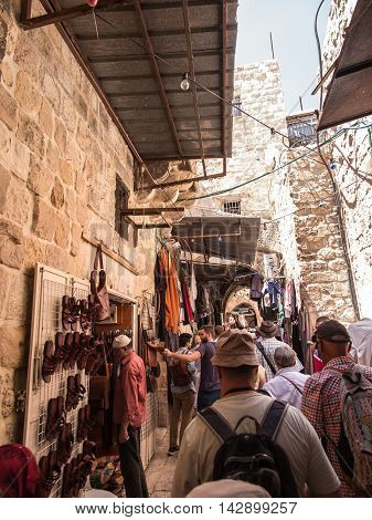 Jerusalem Israel - July 15 2015: Narrow stone street among stalls with traditional souvenirs and goods at bazaar in Old City and children at play - popular place among tourists and pilgrims visiting Jerusalem.