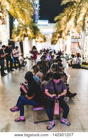 Bangkok Thailand - Aug 17 2016: People addicted to smartphone game Pokemon Go gathered at the park outside Siam Paragon shopping mall