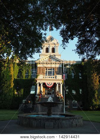 The old Crook County Courthouse in Prineville in Central Oregon is beautifully lit as the sun goes down. The railings on the steps have flower baskets the American flag flies at half-mast and the fountain flows.