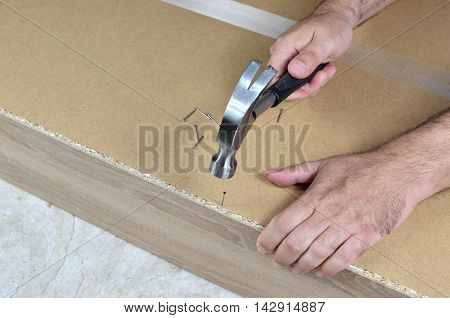 Hammering a nail in back side of a new locker