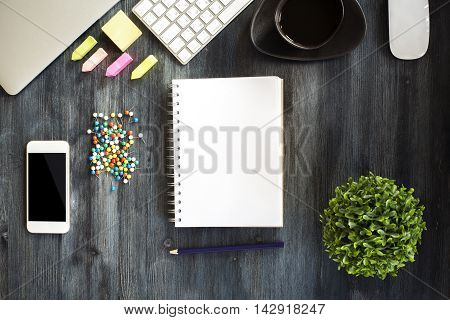 Blank spiral notepad cellular phone colorful pins plant closed laptop keyboard coffee cup and supplies on dark wooden table. Top view Close up Mock up