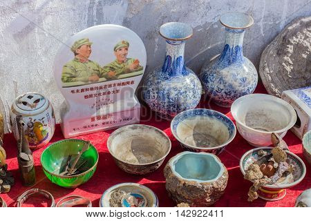 08/10/2016 Likeng China - Dirty old goods and political painting from Mao on a local Chinese market on a sunny day in Likeng