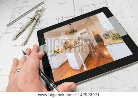 Hand of Architect on Computer Tablet Showing Custom Kitchen Photo Over House Plans, Compass and Ruler.