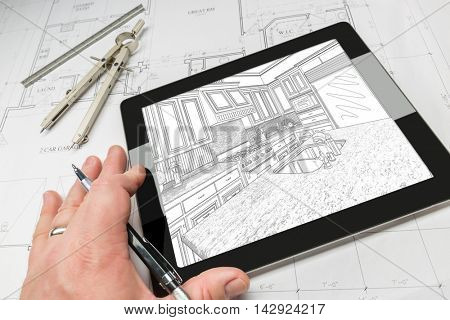 Hand of Architect on Computer Tablet Showing Custom Kitchen Illustration Over House Plans, Compass and Ruler.
