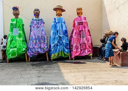 Parramos Guatemala - May 29 2016: Locals wait outside church during Corpus Christi mass next to giant puppets called gigantes used for folk dances.