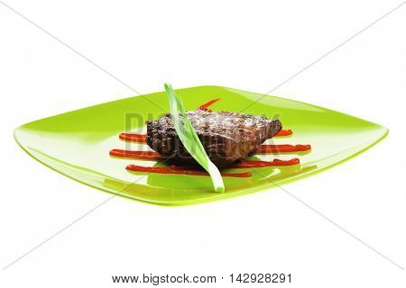 meat savory : grilled beef fillet mignon served on green plate isolated over white background with chives and ketchup