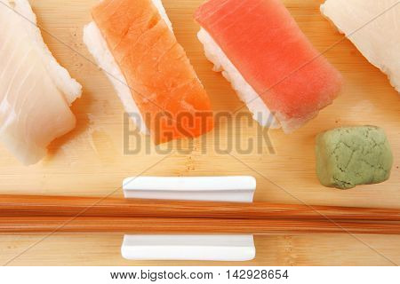 Japanese Cuisine - Set of Tuna (maguro) Salmon (sake) and Eel (unagi) Nigiri Sushi  with Wasabi on wooden plate isolated over white background