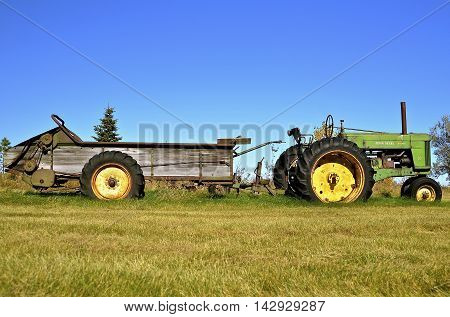DOWNER, MINNESOTA, October 10, 2015: A John Deere Diesel 70 pulling a manure spreader is a product of John Deere Co, an American corporation that manufactures agricultural, construction, forestry machinery, diesel engines, and drivetrains.
