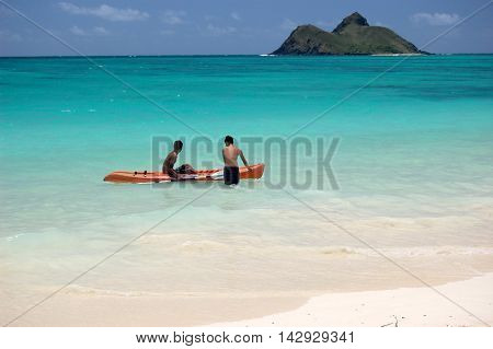 Young boys jumping into a kayak on the turquoise ocean of Lanikai beach, with island at the horizon, Oahu, Hawaii