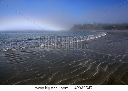 The misty shoreline on a beach at Tofino British Columbia Canada shot in the morning.