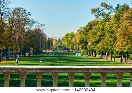 Autumn Park at sunset. Autumn landscape. background with relaxing people on the grass. Bulgaria Sofia park Borisova Gradina