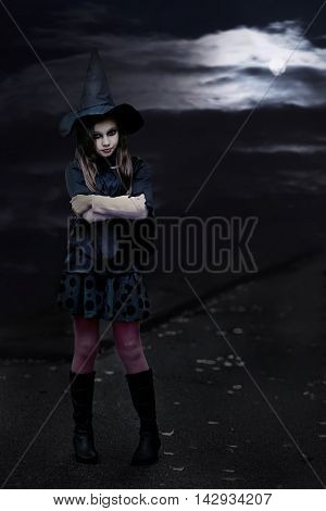 Portrait of a teenage girl in full length in witch costume. Halloween celebration