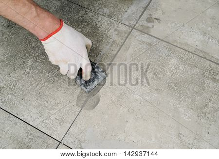 Grouting ceramic tiles. Tilers filling the space between tiles using a rubber trowel.