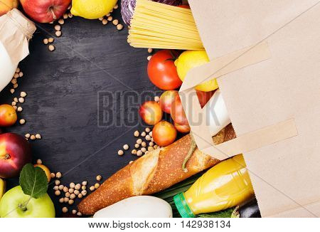 Full paper bag with different helpful food on dark surface with copy space top view. Food background