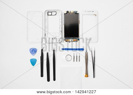Repairman workplace with phone and special tools, flat lay. Top view on disassembled smartphone with instruments on white background, free space. Electronics repair service, device production concept