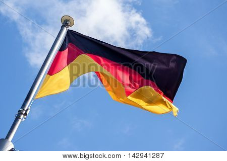 German flag fluttering in the wind against the blue sky with light clouds diagonal view from below soft motion blur