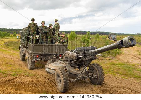 PABRADE / LITHUANIA - AUGUST 7, 2016: Portuguese soldiers stands on a military truck with a field howitzer on multinational exercise