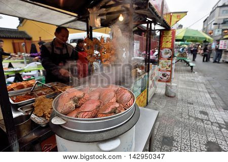 SUZHOU CHINA - MARCH 22: Unidentified Chinese people trade food on March 22 2016 in China. Suzhou is a major economic center and focal point of trade and commerce in Jiangsu Province China