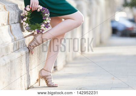 Young lovely woman with a nice flower circlet leaning against a wall.