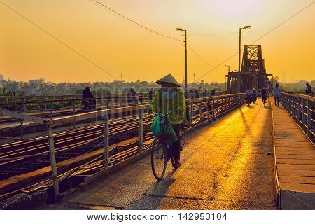 Hanoi,Vietnam - 18 November,2012: The woman and other people go home in the sunset at Long Bien bridge
