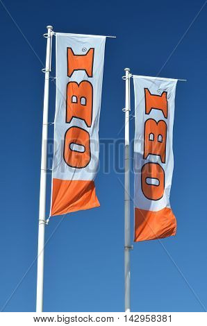 CIRCA AUGUST 2016 - GDANSK: sign of OBI on waving flags against blue sky. OBI is the largest do it yourself retailer in Europe. It was founded in 1970 in Hamburg, Germany.
