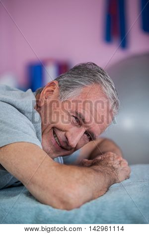 Portrait of senior man lying on a massage bed in clinic