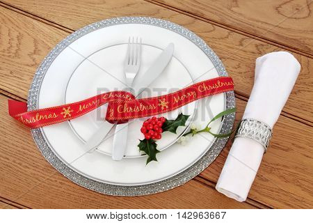Simple christmas dinner table setting with white porcelain plates, red ribbon, knife and fork, linen serviette and silver ring and holly over oak background.
