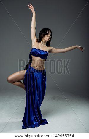 Beautiful young woman dancer in blue top, long blue skirt dancing.