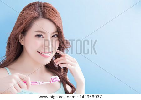 Beautiful young woman with health teeth and charming smile.holding the tooth brush Isolated over blue background asian beauty