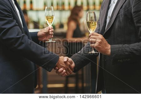 Hands of men shaking hands and drinking white wine
