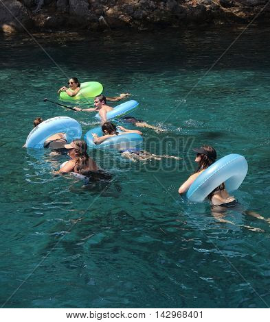 22ND JULY 2016,FETHIYE, TURKEY: A group of tourists swimming and using rubber rings as floatation aids in the sea while on vacation in Fethiye, Turkey , 22nd july 2016