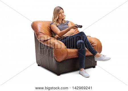 Bored woman seated on an armchair holding a TV remote controller isolated on white background