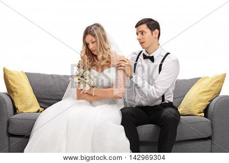 Young groom trying to confort his sad bride isolated on white background