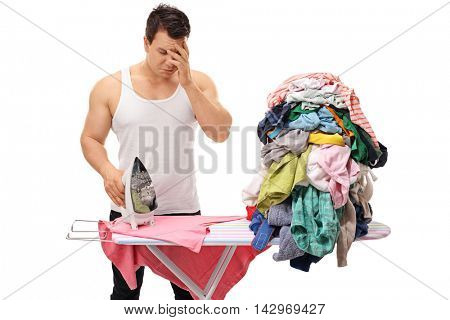 Sad young man posing next to a pile of clothes and an ironing board isolated on white background