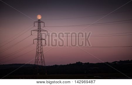 A full moon and an electrical stanchion at dusk